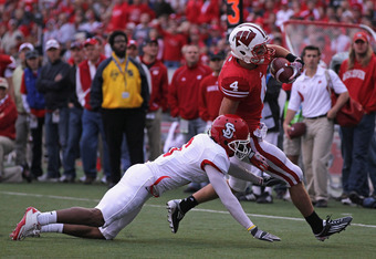 MADISON, WI - SEPTEMBER 24:  Jared Abbrederis #4 of the Wisconsin Badgers is hit by Dametrius Turner #6 of the South Dakota Coyotes at Camp Randall Stadium on September 24, 2011 in Madison Wisconsin. Wisconsin defeated South Dakota 59-10.  (Photo by Jonat