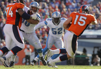 DENVER, CO - OCTOBER 30:  Linebacker Justin Durant #52 of the Detroit Lions tries to contain quaterback Tim Tebow #15 of the Denver Broncos as offensive lineman Orlando Franklin #74 of the Denver Broncos blocks Ndamukong Suh #90 of the Detroit Lions at Sp