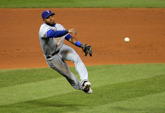 ST LOUIS, MO - OCTOBER 28: Elvis Andrus #1 of the Texas Rangers throws to first on an infield single by Lance Berkman #12 of the St. Louis Cardinals in the seventh inning during Game Seven of the MLB World Series at Busch Stadium on October 28, 2011 in St