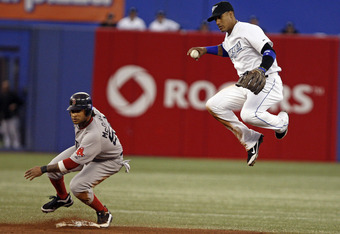 TORONTO, CANADA - SEPTEMBER 8:  Darnell McDonald #54 of the Boston Red Sox is out at second base as Yunel Escobar #5 of the Toronto Blue Jays throws to first trying to make the double play during MLB action at the Rogers Centre September 8, 2011 in Toront