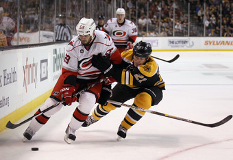 BOSTON, MA - OCTOBER 18:  Chad LaRose #59 of the Carolina Hurricanes tries to keep the puck from Andrew Ference #21 of the Boston Bruins on October 18, 2011 at TD Garden in Boston, Massachusetts.  (Photo by Elsa/Getty Images)