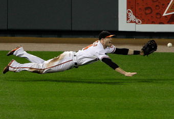 BALTIMORE, MD - SEPTEMBER 28: Leftfielder Nolan Reimold #14 of the Baltimore Orioles misses a hit by Carl Crawford #13 of the Boston Red Sox during the eighth inning at Oriole Park at Camden Yards on September 28, 2011 in Baltimore, Maryland. The Orioles