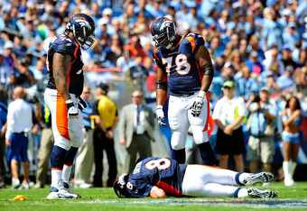 NASHVILLE, TN - SEPTEMBER 25:  Quarterback Kyle Orton #8 of the Denver Broncos lays on the ground in front of teammates Orlando Franklin #74 and Ryan Clady #76 after drawing a roughing the passer call against the Tennessee Titans during the first half at