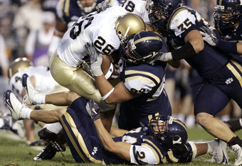 PROVO, UT - SEPTEMBER 4:  Thomas Travis #26 of Notre Dame gets tackled by Manaia Brown #99, Cameron Jensen #35 and Spencer White #24 of BYU September 4, 2004 at Lavell Edwards Stadium in Provo, Utah.  (Photo by George Frey/Getty Images)