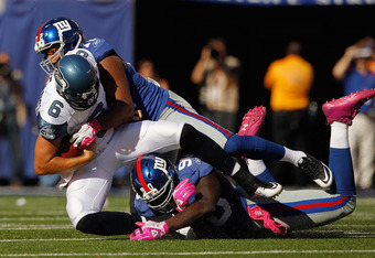 EAST RUTHERFORD, NJ - OCTOBER 09:  Charlie Whitehurst #6 of the Seattle Seahawks is sacked by Osi Umenyiora #72 of the New York Giants and teammate  Jason Pierre-Paul #90 at MetLife Stadium on October 9, 2011 in East Rutherford, New Jersey.  (Photo by Mik