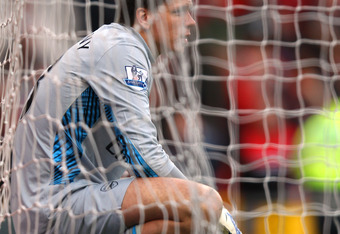 MANCHESTER, ENGLAND - AUGUST 28:  Wojciech Szczesny of Arsenal looks dejected as he sits in the back of the net after conceding the eighth goal during the Barclays Premier League match between Manchester United and Arsenal at Old Trafford on August 28, 20