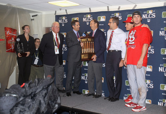 MILWAUKEE, WI - OCTOBER 16:  The National League Championship trophy is presented to Bill DeWitt Jr., Chairman & Chief Executive Officer of the St. Louis Cardinals after they won 12-6 against the Milwaukee Brewers during Game Six of the National League Ch