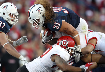 TUCSON, AZ - NOVEMBER 05:  Runningback Taimi Tutogi #31 of the Arizona Wildcats dives over the pile for a first down against the Utah Utes during the college football game at Arizona Stadium on November 5, 2011 in Tucson, Arizona.  The Utes defeated the W