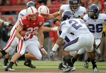 LINCOLN, NE - NOVEMBER 05: Running back Rex Burkhead #22 of the Nebraska Cornhuskers tries to avoid defensive back Ibraheim Campbell #24 of the Northwestern Wildcats during their game at Memorial Stadium November 5, 2011 in Lincoln, Nebraska.  Northwester