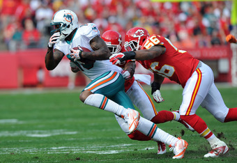 KANSAS CITY, MO - NOVEMBER 06:  Wide receiver Brandon Marshall #19 of the Miami Dolphins rushes around linebacker Derrick Johnson #56 of the Kansas City Chiefs after catching a pass, during the first quarter on November 6, 2011 at Arrowhead Stadium in Kan