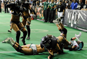 LAS VEGAS, NV - FEBRUARY 06:  Quarterback Ashley Salerno #8 of the Los Angeles Temptation dives past Whitney Paronish #16 and Marirose Roach #6 of the Philadelphia Passion to score on a conversion attempt during the Lingerie Football League's Lingerie Bow