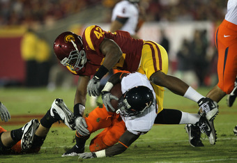 LOS ANGELES, CA - SEPTEMBER 11:  Linebacker Devon Kennard #42 of the USC Trojans tackles running back  Perry Jones #33 of the Virginia Cavaliers at Los Angeles Memorial Coliseum on September 11, 2010 in Los Angeles, California.  (Photo by Stephen Dunn/Get