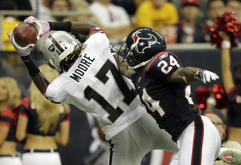 HOUSTON - OCTOBER 09: Wide receiver Denarius Moore #17 of the Oakland Raiders catches a pass as he is defended by cornerback Johnathan Joseph #24 of the Houston Texans at Reliant Stadium on October 9, 2011 in Houston, Texas. (Photo by Bob Levey/Getty Imag