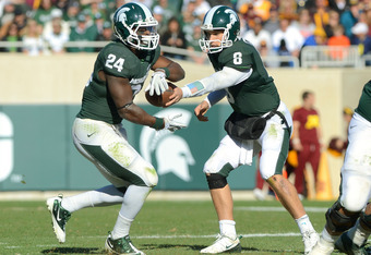 EAST LANSING, MI - NOVEMBER 05:  Kirk Cousins #8 of the Michigan State Spartans hands the football off to Le'Veon Bell #24 on a fourth quarter play against the Minnesota Golden Gophers at Spartan Stadium on November 5, 2011 in East Lansing, Michigan. The