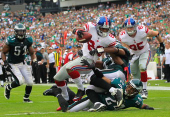 PHILADELPHIA, PA - SEPTEMBER 25:  Victor Cruz #80 of the New York Giants catches a 28 yard touchdown pass in the fourth quarter over Nnamdi Asomugha #24 of the Philadelphia Eagles  at Lincoln Financial Field on September 25, 2011 in Philadelphia, Pennsylv