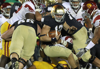 SOUTH BEND, IN - OCTOBER 22:  Andrew Hendrix #12 of the Notre Dame Fighting Irish is stopped short of the goal by defensive players from the University of Southern California Trojans including Nick Perry #8 at Notre Dame Stadium on October 22, 2011 in Sou