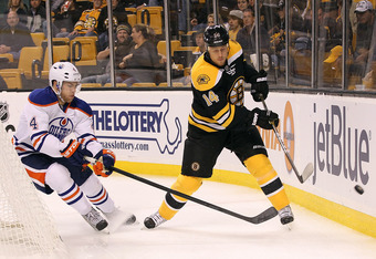 BOSTON,  MA - OCTOBER 10:  Taylor Hall #4 of the Edmonton Oilers battles Joe Corvo #14 of the Boston Bruins for control of the punk TD Garden on October 10, 2011 in Boston, Massachusetts. (Photo by Jim Rogash/Getty Images)