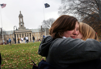 STATE COLLEGE, PA - NOVEMBER 11: Penn State Concert Choir members Laurel Smail (L) and Alison Geesey hug after singing the school alma mater on campus in the wake of the Jerry Sandusky scandal on November 11, 2011 in State College, Pennsylvania. The choir