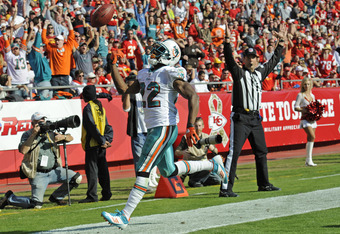 KANSAS CITY, MO - NOVEMBER 06:  Running back Reggie Bush #22 of the Miami Dolphins tosses the ball into the air after scoring a touch down against of the Kansas City Chiefs during the third quarter on November 6, 2011 at Arrowhead Stadium in Kansas City,