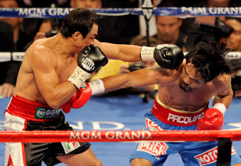 LAS VEGAS, NV - NOVEMBER 12:  (L-R) Juan Manuel Marquez connects with a left to the head of Manny Pacquiao during the WBO world welterweight title fight at the MGM Grand Garden Arena on November 12, 2011 in Las Vegas, Nevada.  (Photo by Ethan Miller/Getty
