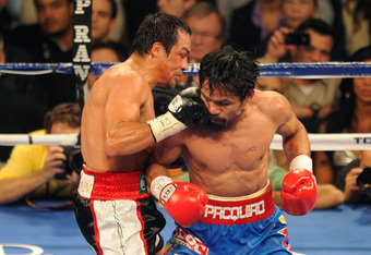 LAS VEGAS, NV - NOVEMBER 12:  (L-R) Juan Manuel Marquez connects with a right to the face of Manny Pacquiao during the WBO world welterweight title fight at the MGM Grand Garden Arena on November 12, 2011 in Las Vegas, Nevada.  (Photo by Ethan Miller/Gett