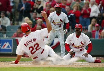 ST. LOUIS, MO - APRIL 5:  Catcher Mike Matheny #22 of the St. Louis Cardinals slides into home plate as his teammate Reggie Sanders #16 looks on during the game against the Milwaukee Brewers on Opening Day at Busch Stadium on April 5, 2004 in St. Louis, M