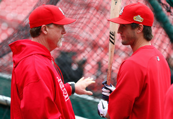 ST LOUIS, MO - OCTOBER 18:  Hitting coach Mark McGwire (L) of the St. Louis Cardinals talk with David Freese during batting practice at Busch Stadium on October 18, 2011 in St Louis, Missouri. The Texas Rangers will take on the St. Louis Cardinals in Game