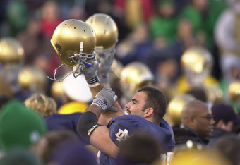 Players salute their fellow students with raised helmets after a victory