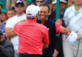 MELBOURNE, AUSTRALIA - NOVEMBER 20:  Tiger Woods of the U.S. Team embraces U.S. Team captain Fred Couples after winning his match on the 15th hole during the Day Four Singles Matches of the 2011 Presidents Cup at Royal Melbourne Golf Course on November 20