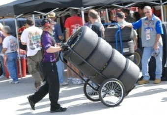 A crew member pushes a hand truck full of tires