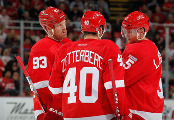 DETROIT, MI - NOVEMBER 03:  Nicklas Lidstrom #5 of the Detroit Red Wings talks with teammates Henrik Zetterberg #40 and Johan Franzen #93 while playing the Calgary Flames at Joe Louis Arena on November 3, 2011 in Detroit, Michigan. Calgary won the game 4-