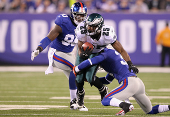 EAST RUTHERFORD, NJ - NOVEMBER 20:  LeSean McCoy #25 of the Philadelphia Eagles runs the ball in the first half against Aaron Ross #31 and Jason Pierre-Paul #90 of the New York Giants at MetLife Stadium on November 20, 2011 in East Rutherford, New Jersey.
