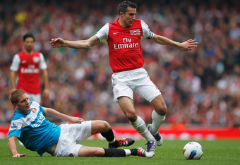 LONDON, ENGLAND - OCTOBER 16:  Robin van Persie of Arsenal is tackled by Michael Turner of Sunderland during the Barclays Premier League match between Arsenal and Sunderland at the Emirates Stadium on October 16, 2011 in London, England.  (Photo by Paul G