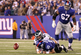 EAST RUTHERFORD, NJ - NOVEMBER 20:  Eli Manning #10 of the New York Giants fumbles the ball late in the fourth quarter against Jason Babin #93 of the Philadelphia Eagles at MetLife Stadium on November 20, 2011 in East Rutherford, New Jersey.  (Photo by Al