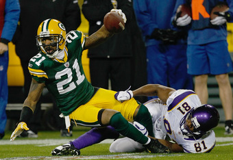 GREEN BAY, WI - NOVEMBER 14: Charles Woodson #21 of the Green Bay Packers intercepts the football as he is tackled by Devin Aromashadu #19 of the Minnesota Vikings at Lambeau Field on November 14, 2011 in Green Bay, Wisconsin. (Photo by Scott Boehm/Getty