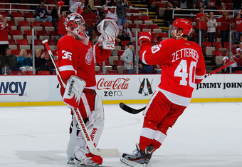 DETROIT, MI - NOVEMBER 08:  Jimmy Howard #35 of the Detroit Red Wings celebrates a 5-2 win over the Colorado Avalanche with Henrik Zetterberg #40 at Joe Louis Arena on November 8, 2011 in Detroit, Michigan. (Photo by Gregory Shamus/Getty Images)