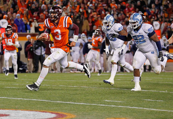 BLACKSBURG, VIRGINIA - NOVEMBER 17:  Quarterback Logan Thomas #3 of the Virginia Tech Hokies runs with the ball for a touchdown as defensive tackle Sylvester Williams #92 of the North Carolina Tar Heels chases at Lane Stadium on November 17, 2011 in Black