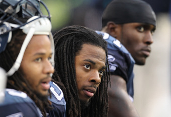 SEATTLE - OCTOBER 30:  (L-R) Richard Sherman #25, Earl Thomas #29, and Kam Chancellor #31 of the Seattle Seahawks look on from the bench near the end of the game against the Cincinnati Bengals at CenturyLink Field on October 30, 2011 in Seattle, Washingto