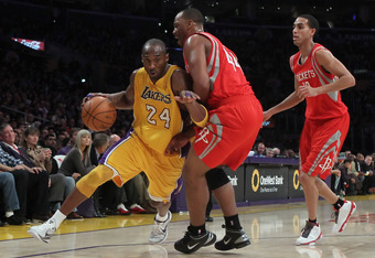 LOS ANGELES, CA - FEBRUARY 01:  Kobe Bryant #24 of the Los Angeles Lakers drives past Chuck Hayes #44 and Kevin Martin #12 of the Houston Rockets in the first half at Staples Center on February 1, 2011 in Los Angeles, California. The Lakers defeated the R