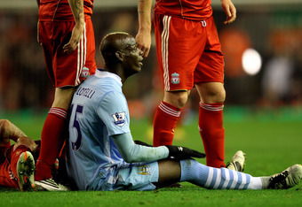 A bemused Mario Balotelli reacts after being shown his second yellow card of the match by referee Martin Atkinson.