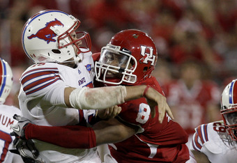 HOUSTON, TX - NOVEMBER 19: Quarterback J.J. McDermott #15 of the Southern Methodist University Mustangs avoids the sack of linebacker Sammy Brown #8 of the Houston Cougars on November 19, 2011 at Robertson Stadium in Houston, Texas. Houston defeated SMU 3