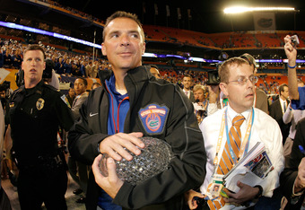 MIAMI - JANUARY 08:  Head coach Urban Meyer of the Florida Gators walks off with the National Championship trophy after their 24-14 win against the Oklahoma Sooners during the FedEx BCS National Championship game at Dolphin Stadium on January 8, 2009 in M