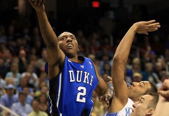 Duke G Nolan Smith scores on a layup over Kendall Marshall
