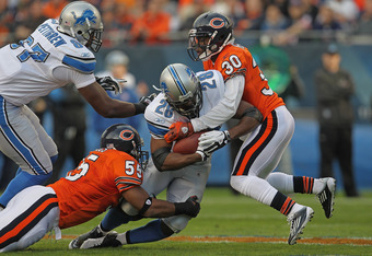 CHICAGO, IL - NOVEMBER 13: Lance Briggs #55 and D.J. Moore #30 of the Chicago Bears bring down Maurice Morris #28 of the Detroit Lions at Soldier Field on November 13, 2011 in Chicago, Illinois. (Photo by Jonathan Daniel/Getty Images)