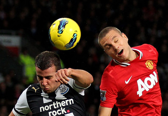 MANCHESTER, ENGLAND - NOVEMBER 26:   Stephen Taylor of Newcastle United goes up for a header with Nemanja Vidic of Manchester United during the Barclays Premier League match between Manchester United and Newcastle United at Old Trafford on November 26, 20
