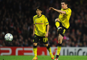 LONDON, ENGLAND - NOVEMBER 23:  Shinji Kagawa of Dortmund looks on as  Robert Lewandowski of Dortmund takes a shot during the UEFA Champions League Group F match between Arsenal FC and Borussia Dortmund  at Emirates Stadium on November 23, 2011 in London,