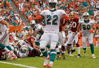 MIAMI GARDENS, FL - NOVEMBER 13:  Reggie Bush #22 of the Miami Dolphins walks into the endzone during a game against the Washington Redskins at Sun Life Stadium on November 13, 2011 in Miami Gardens, Florida.  (Photo by Mike Ehrmann/Getty Images)
