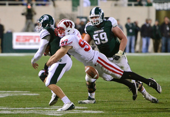 EAST LANSING, MI - OCTOBER 22:  Brendan Kelly #97 of the Wisconsin Badgers knocks the ball away from quarterback Kirk Cousins #8 of the Michigan State Spartans on a play in the fourth at Spartan Stadium on October 22, 2011 in East Lansing, Michigan. The S