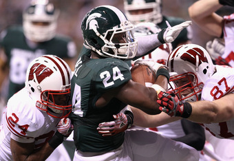 INDIANAPOLIS, IN - DECEMBER 03:  Le'Veon Bell #24 of the Michigan State Spartans scores a 6-yard rushing touchdown against Shelton Johnson #24 and  Ethan Hemer #87 of the Wisconsin Badgers during the second quarter of the Big 10 Conference Championship Ga