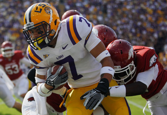 BATON ROUGE, LA - NOVEMBER 25:  Kick returner Tyrann Mathieu #7 of the LSU Tigers returns a punt for seven yards as he is tackled by Marquel Wade #1 of the Arkansas Razorbacks at Tiger Stadium on November 25, 2011 in Baton Rouge, Louisiana.  (Photo by Chr